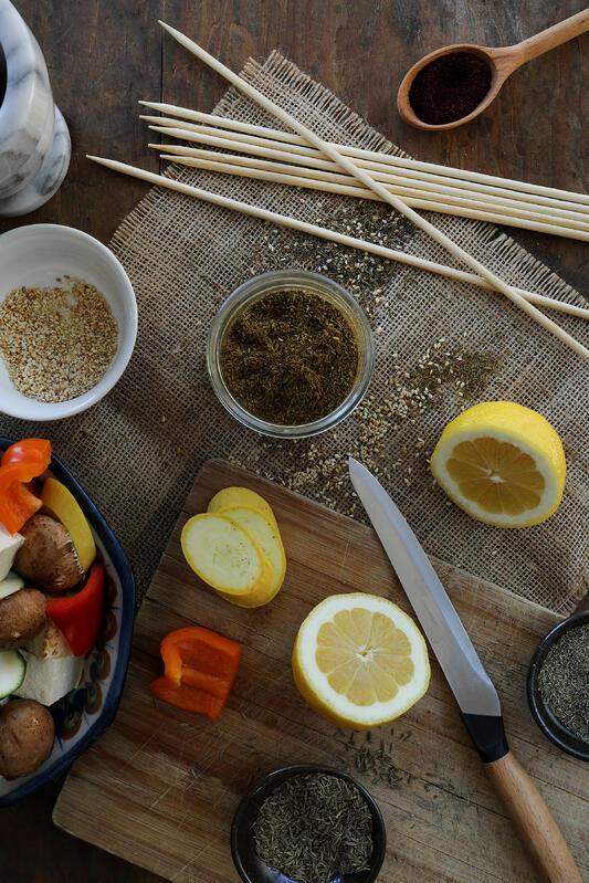 Fresh ingredients and spices are laid out on a cutting board and mat. Colorful vegetables are ready for skewering.