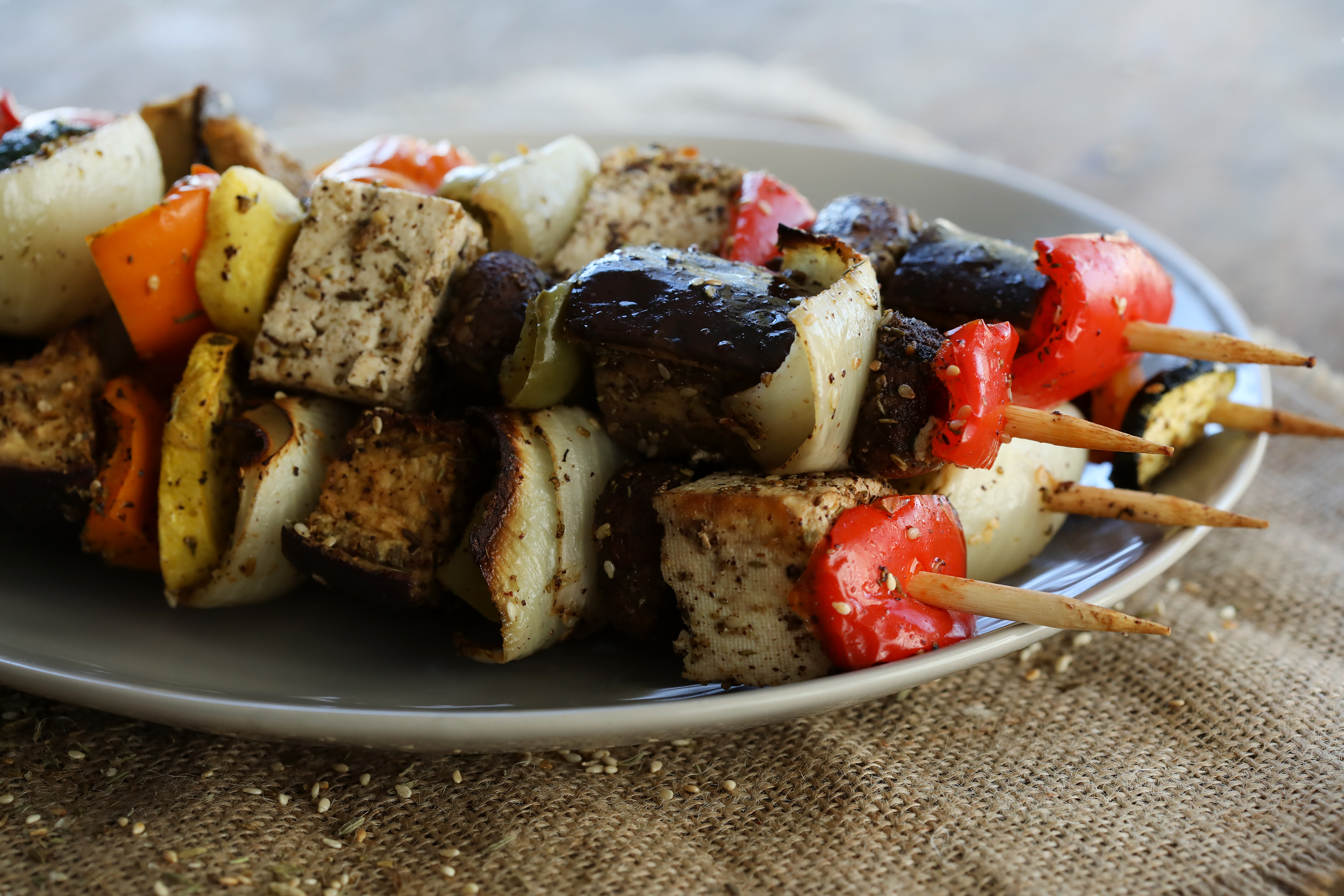 Grilled vegetable kebabs with peppers, zucchini, eggplant, and onion, resting on a plate