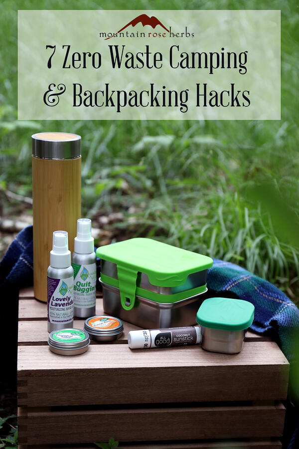 Assorted low waste camping supplies arranged on a wooden side table outdoors. Stainless steel food storage and natural outdoors products. Bamboo tea tumbler. Pinterest link to Mountain Rose Herbs.