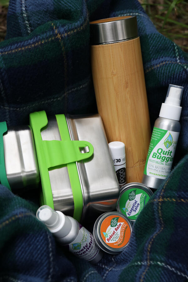 Various products are packed into a hiking backpack for an outdoor adventure. Bamboo tea tumbler, stainless steel food containers, and reusable tins and bottles for outdoor use.