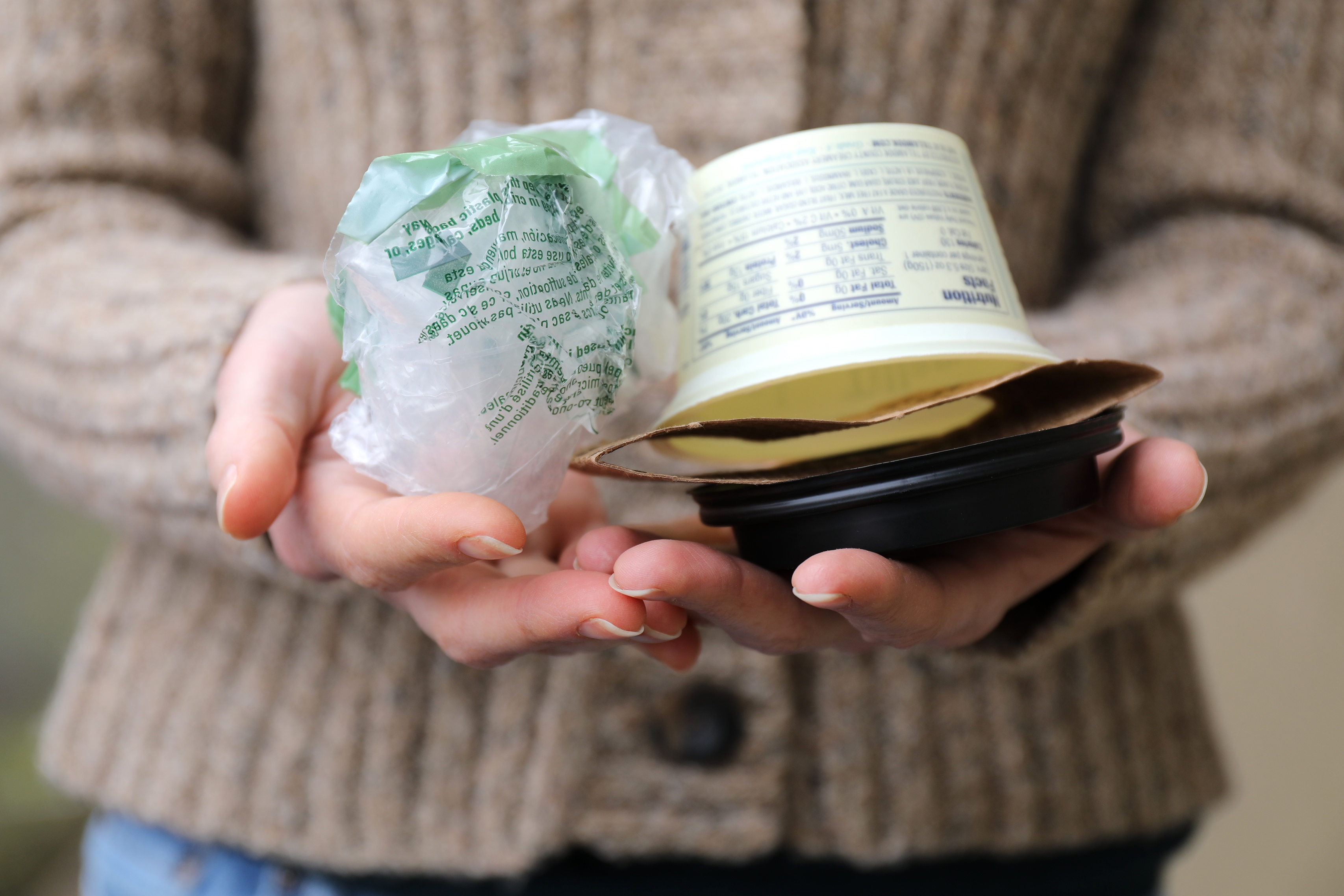 Hands holding plastic grocery bag and yogurt container and coffee holder in palm of hands
