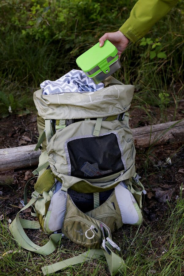 A tan hiking backpack with low waste impact being packed on a forest trail. Portable food containers are packed with first aid.