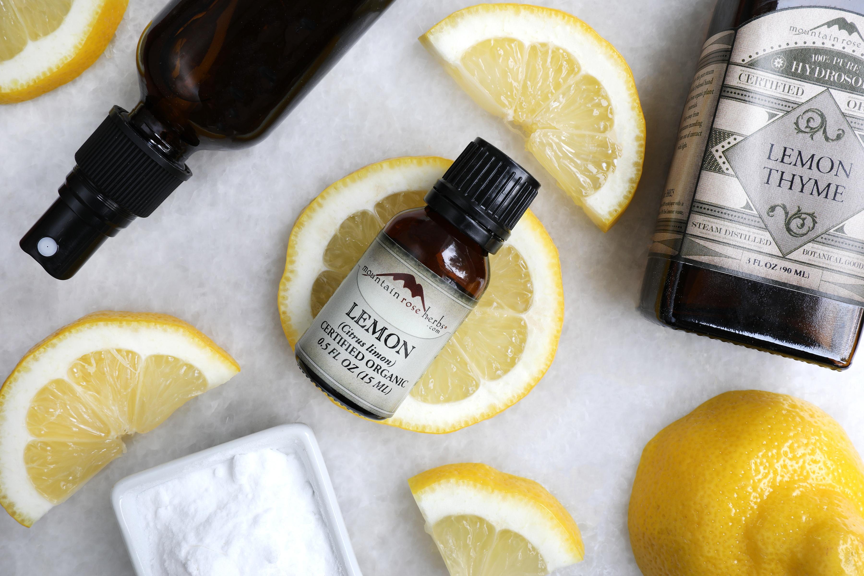 Glass bottles with organic lemon essential oil with fresh lemon wedges