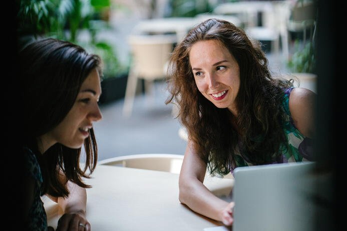 Two young women searching the internet for online resources geared towards herbalism and naturopathy.