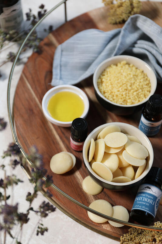 Small bowls of body care ingredients including cocoa butter wafers, oil, and beeswax pastilles.