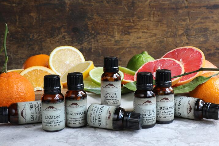 Group of citrus essential oils on counter with fresh citrus fruit