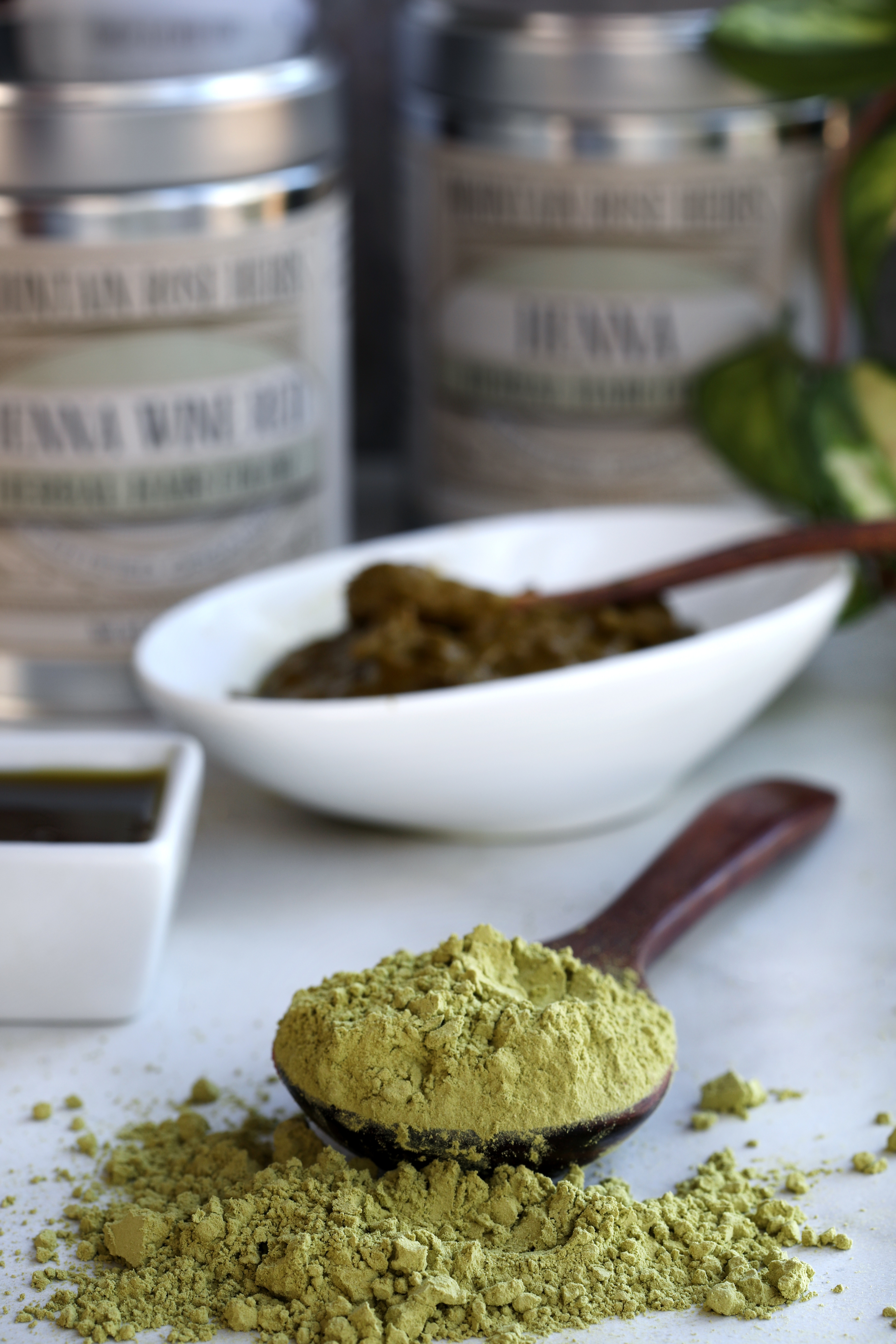 Spoon with green powder spilling out with henna tins and mixing bowl in background