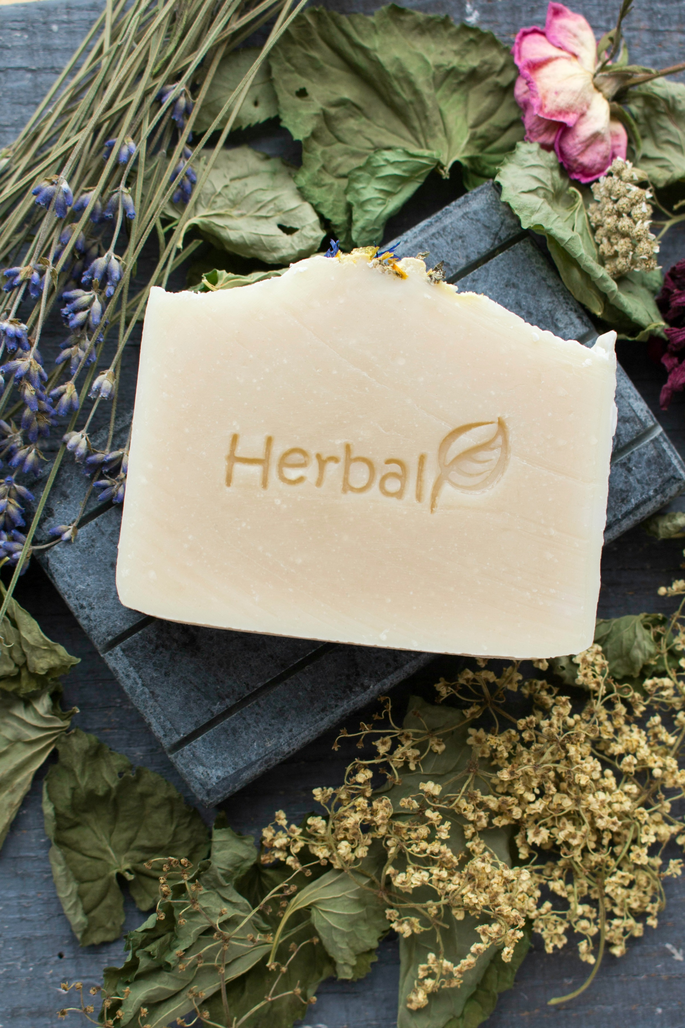 Bar of homemade herbal soap laying on a pile of dried herbs, leaves, flowers