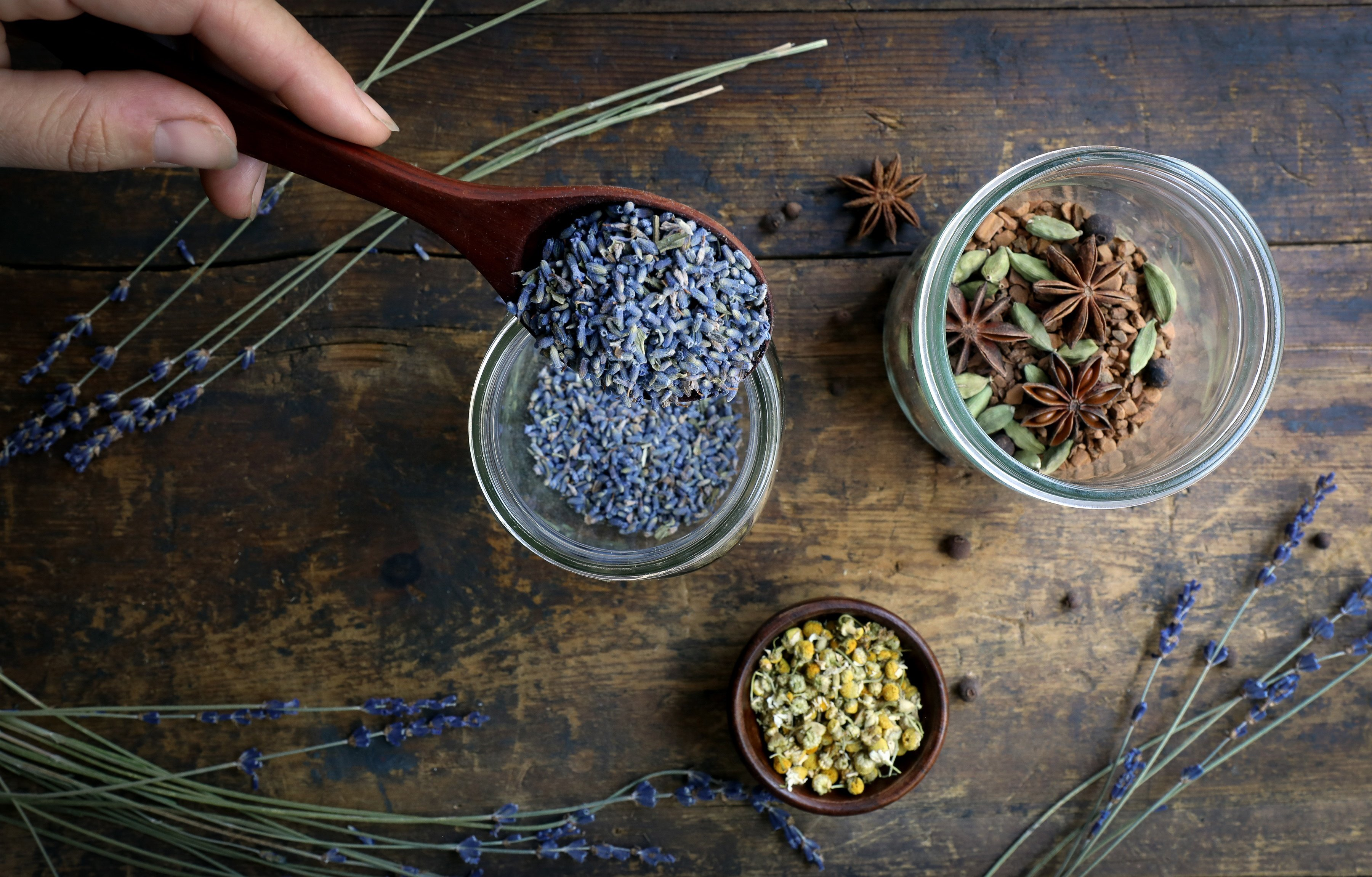Hand pouring lavender into jar with sprigs of lavender on table and small bowl of chamomile flowers. Another jar with warming spices.