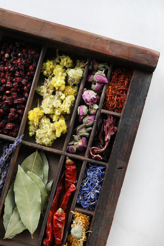 Colorful herbs displayed in rustic wooden box.