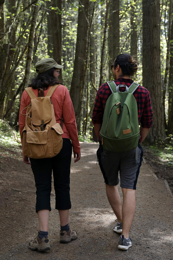 A young man and young woman hiking a forest trail with lightweight backpacks.