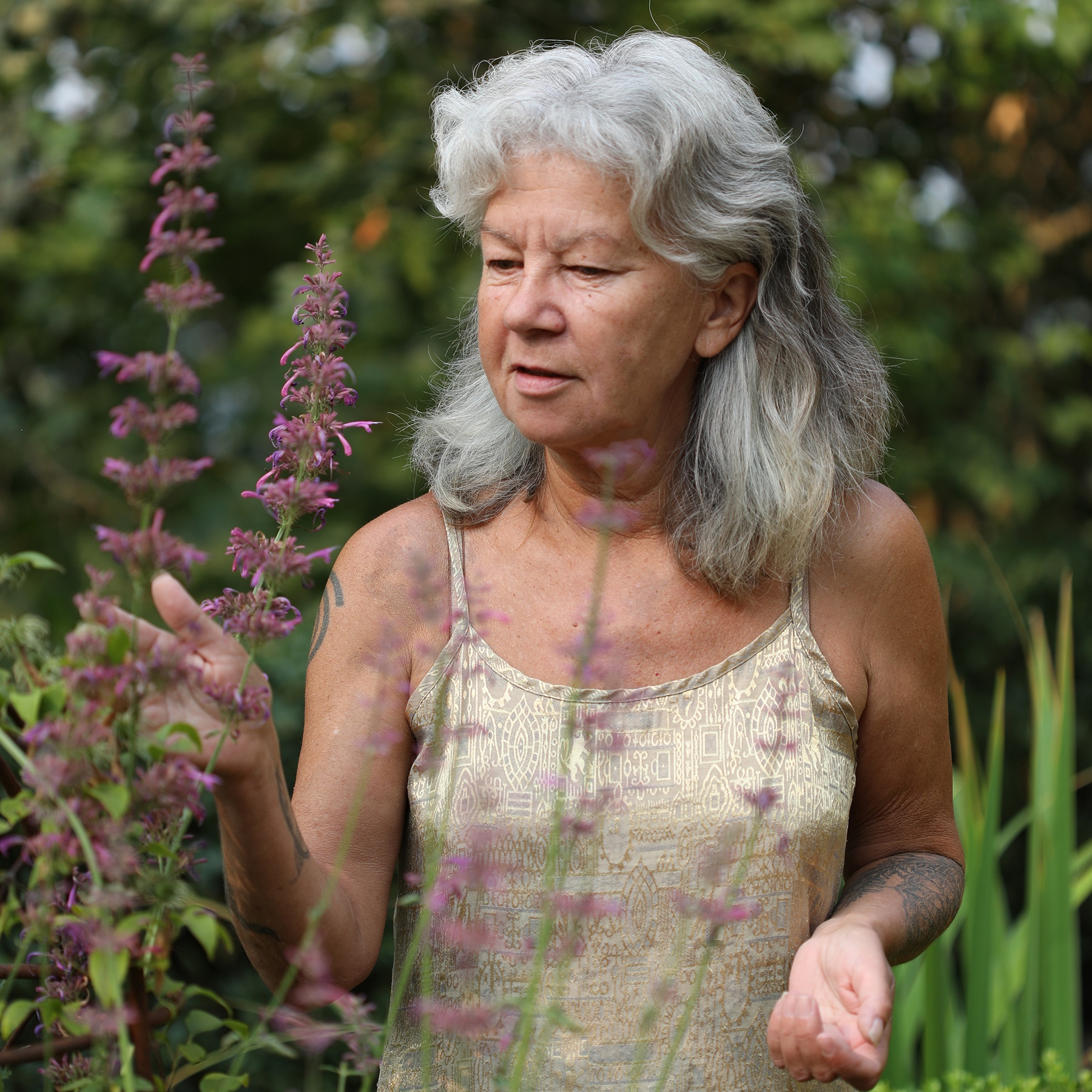 Mountain Rose Herbs co owner, Julie Bailey, standing in garden with hands touching fresh herbs