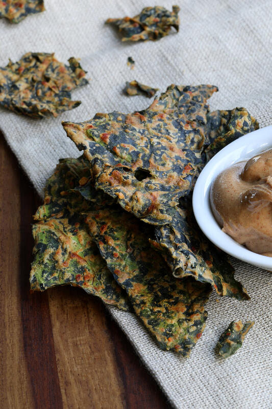 Detailed photograph of crispy kale chips and a bowl of spiced butter on a burlap table cloth.