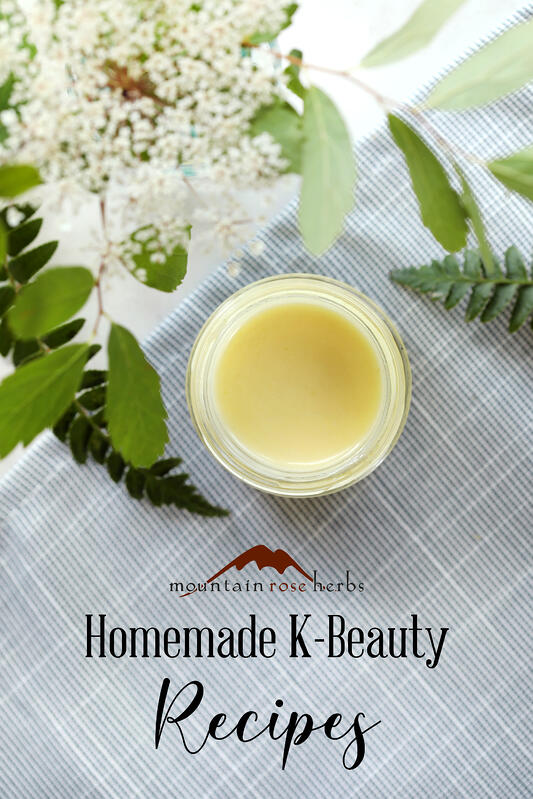Pinterest link to Mountain Rose Herbs. Finished propolis and chamomile skin cream emulsion is arranged with fresh foliage and a blue serviette on a marble counter top.