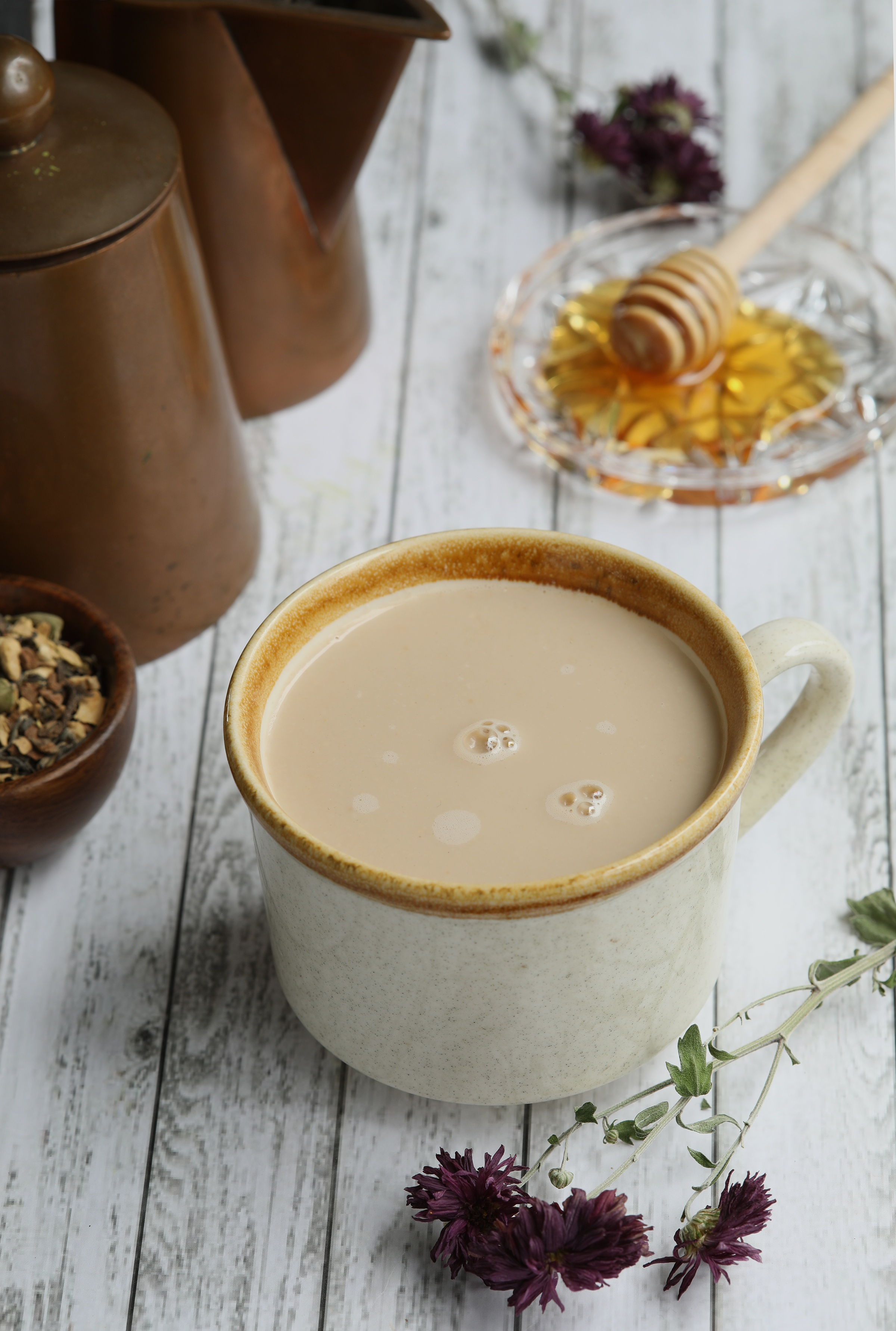 Creamy Maca Latte in mug on wooden table with chai tea and honey