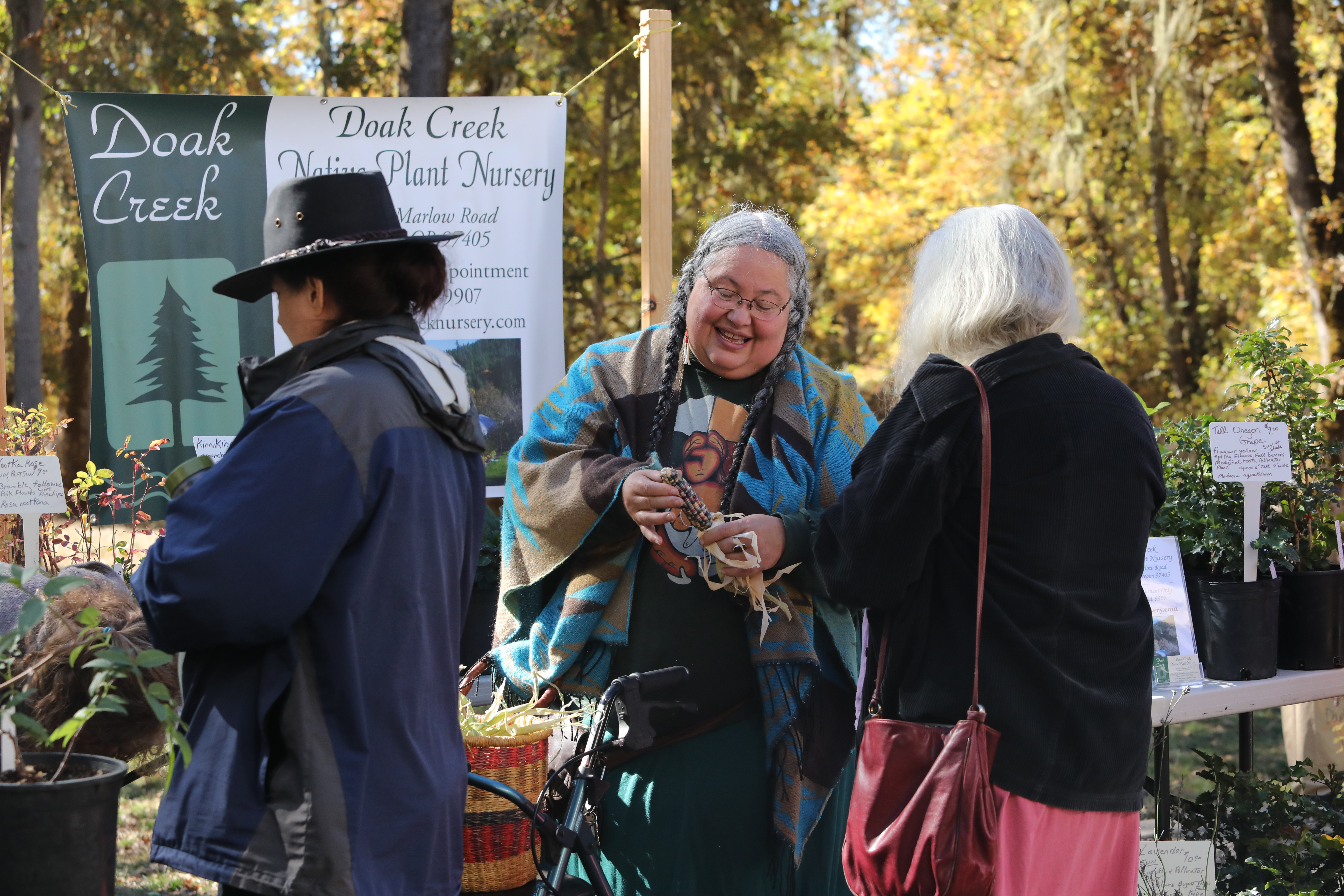 Three people in an autumnal outdoor setting attending a plant sale.