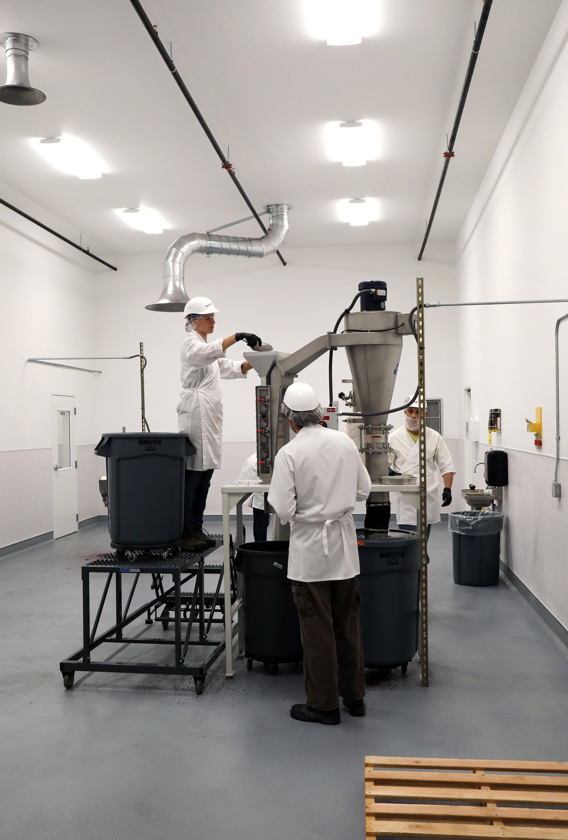 Three workers in lab coats and hard hats operating mill equiptment