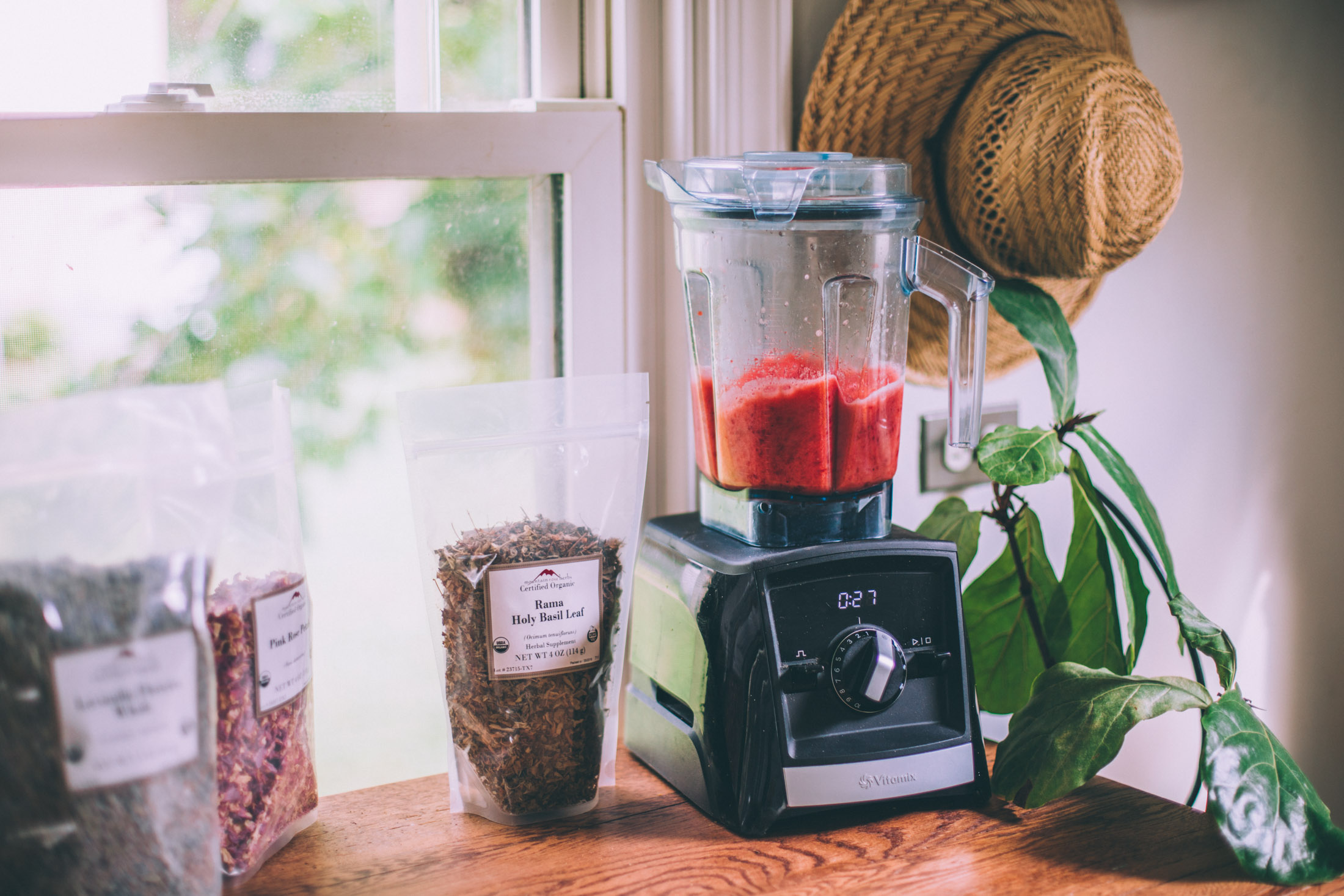 Preparations for making blended agua frescas. A Vitamix blender and bags of dried herbs like holy basil and rose petals.