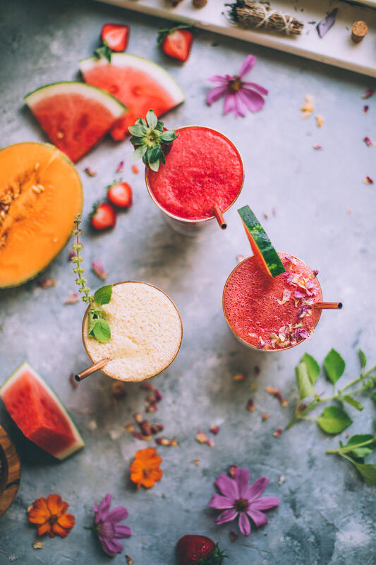 An assortment of fresh fruits, flowers, and herbs are gathered with three completed summer agua frescas garnished with strawberries, watermelon, and mint.
