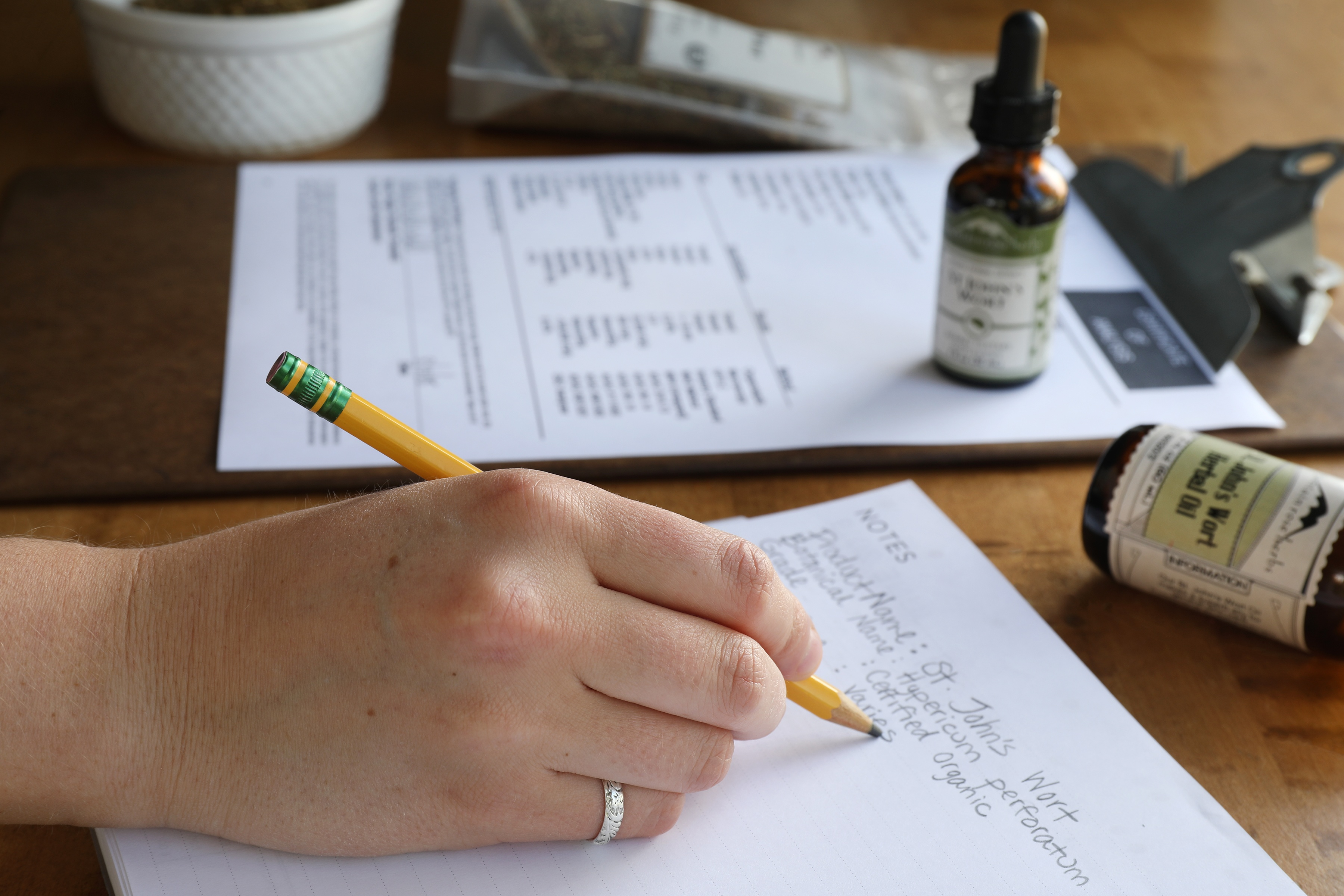 Hand holding pencil writing notes about Certificate of Analysis
