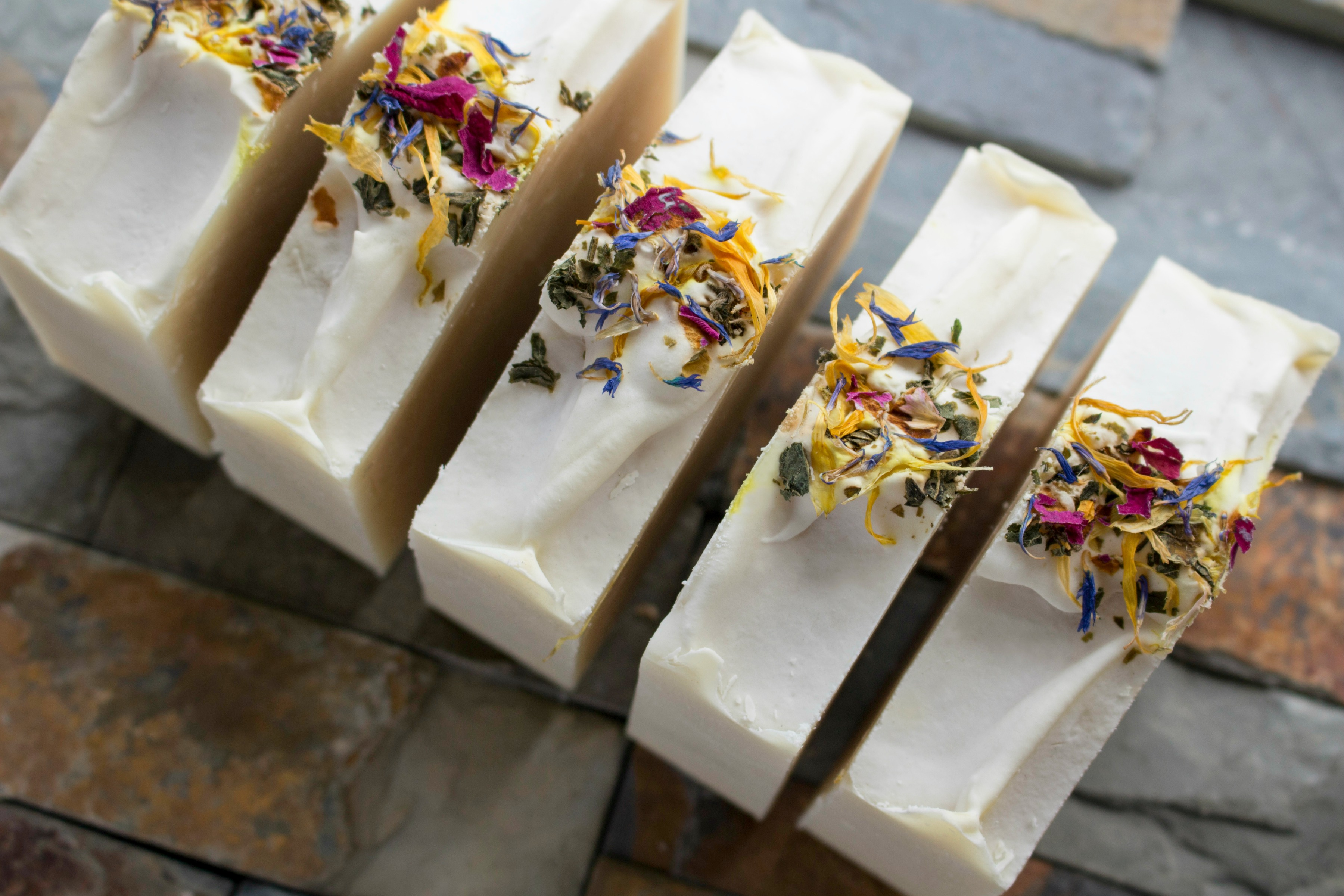 White bars of soap sprinkled with colorful flower petals on a cool-colored natural stones.