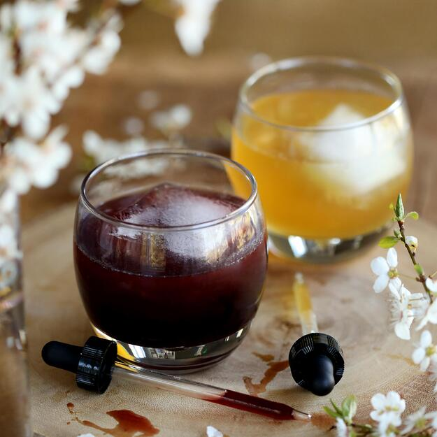 Two colorful drinks with white flowers and a medicine dropper