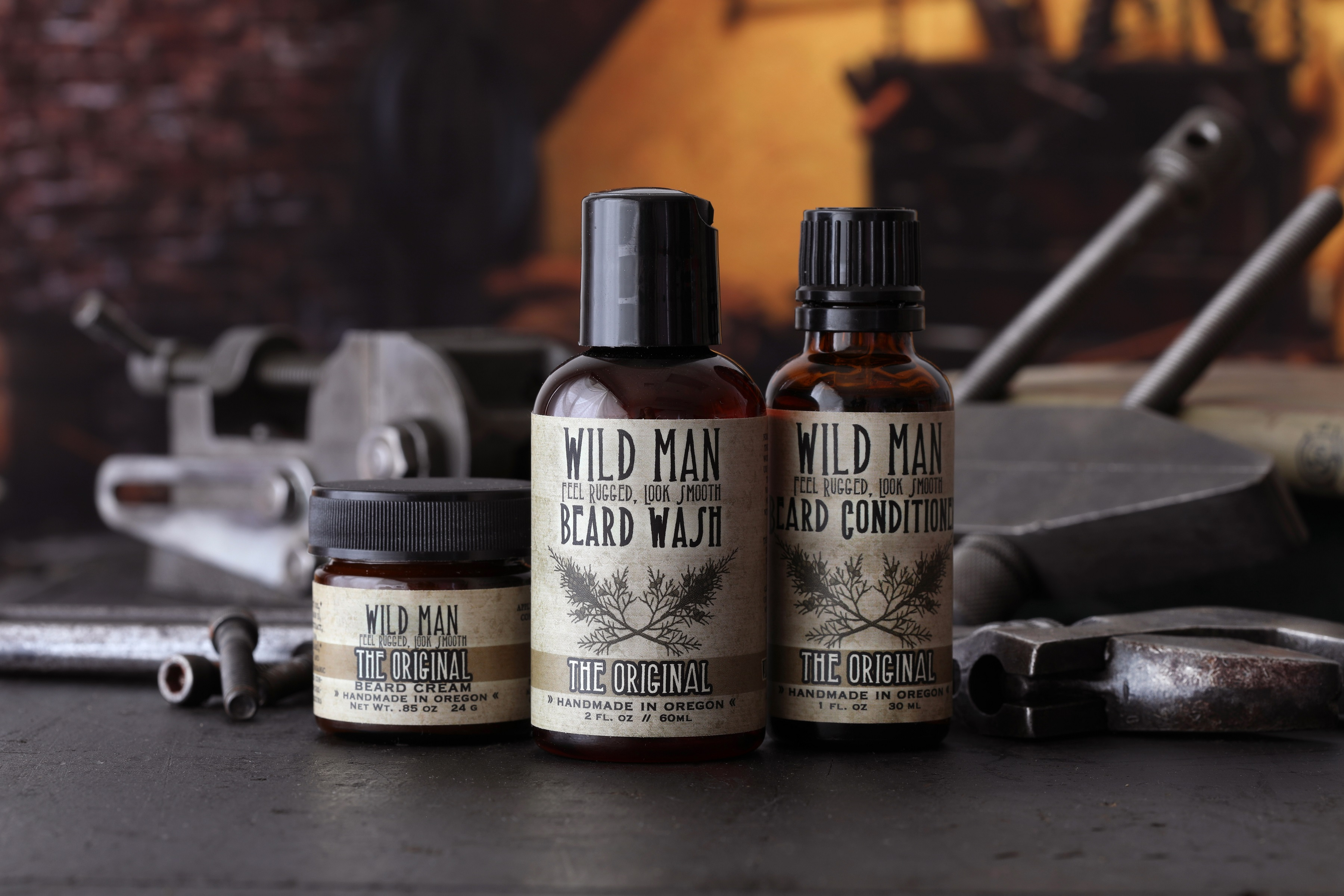 3 beard care products with dark workshop background surrounded by tools